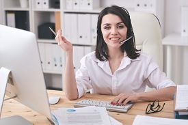 Young smiling customer support representative looking at you while sitting by workplace in front of computer screen and consulting clients