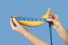 Measuring The Size Of A Banana As A Symbol Of The Male Penis Isolated On Blue Background. Big Dick L