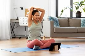 sport, fitness and healthy lifestyle concept - happy smiling young african american woman with tablet pc computer stretching arm at home