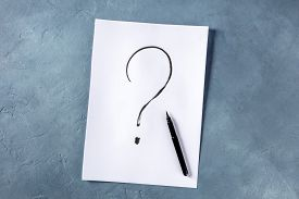 Question Mark, Written In Ink On A Piece Of Standard Office Paper, Shot From The Top On A Blue Backg