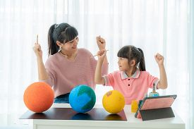 Asian Elementary Schoolgirl With Mother Painting The Moon In Science Class Learning About The Solar