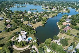 Aerial view of a tree-lined, upscale suburban neighborhood with lakes in summer.