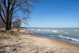 A family walks along a Lake Michigan beach in Wilmette, Illinois with other people nearby while attempting to social distance during the coronavirus pandemic of 2020.