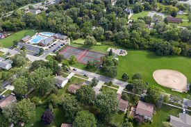 Aerial view of a tree-lined neighborhood with a ballfield, tennis courts and swimming pool in a Chicago suburb during summer.