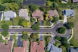 Aerial view of a tree-lined neighborhood in a cul-de-sac in a Chicago suburban city in summer.