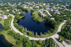 Aerial view of a tree-lined, upscale suburban neighborhood with pond in summer.