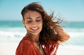 Latin fashion woman wearing red lace dress at beach and enjoy fresh breeze. Portrait of carefree tanned girl relaxing at beach during summer vacation. Young smiling beauty woman during summer holiday.