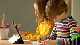 Distance Learning For Schoolchildren During The Coronavirus Quarantine Period. Children Are Sitting
