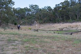 A Fisherman Walking Through Dry Bushland Towards A Fresh Water Reservoir To Locate A Suitable Fishin