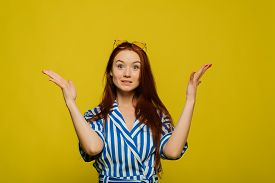 A Redhead Girl Is On The Yellow Background. A Redhead Girl With Glasses On Her Head. Surprised Girl