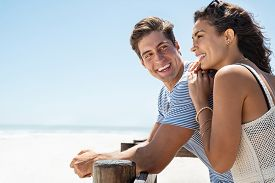 Loving couple standing at beach shore while looking away with copy space. Young man looking at beautiful woman on beach while she is contemplating the future. Boyfriend and girlfriend enjoying summer.