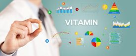 Nutritionist giving you a pill with VITAMIN inscription, healthy lifestyle concept