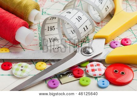 Sewing Items: Buttons, Colorful Fabrics, Scissors, Measuring Tape, Thimble, Spools Of Thread