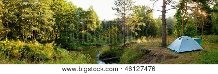 Camping Tent By River In Forest