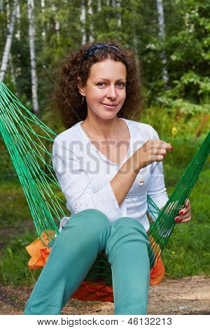 Young smiling woman sits in hammock with yellow flower she holds in her hand