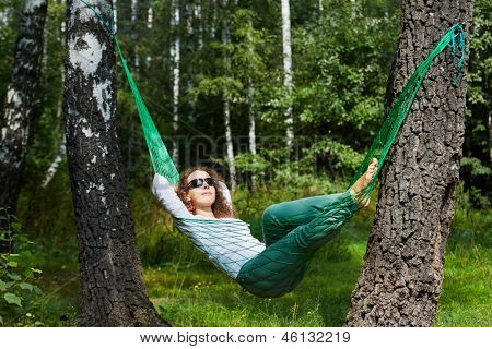 Young smiling woman in dark sunglasses lies in hammock, turning his face to the sun and putting her hands behind her head