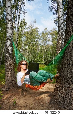 Young barefooted woman in dark sunglasses lies in hammock at birchwood and works on notebook