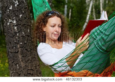 Young woman lies in hammock suspended between two thick birches and reads book