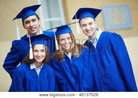 Friendly students in graduation gowns looking at camera