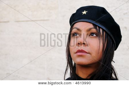 "Young lady wearing black jacket and hat looking out of frame with a reference to Ernesto ""Che"" Guevara in style poster"