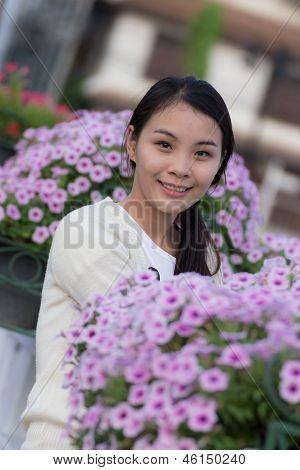 Chica tailandesa con flores violetas de Petunia