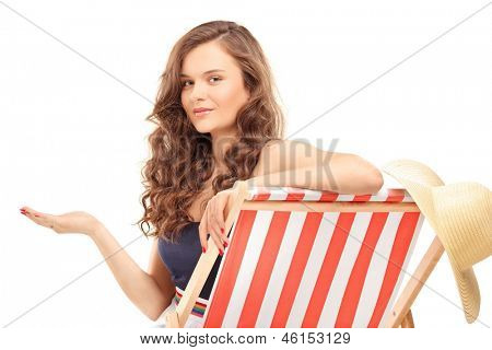 Beautiful young woman sitting on a sun lounger and gesturing with hand, isolated on white background