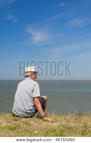 Elderly man is sitting on Dutch dyke in Lauwersoog