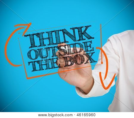 Businesswoman writing think outside the box with a chalk on blue background