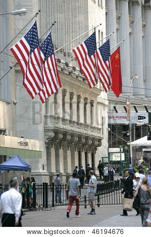 NEW YORK - MAY 30: Pedestrians walk along Broad Street past the New York Stock Exchange on May 30, 2013 in New York City. The Exchange building was built in 1903.