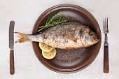 Grilled fish with lemon and rosemary on brown plate with antique cutlery isolated on white wooden background with clipping path top view. Mediterranean seafood background. poster