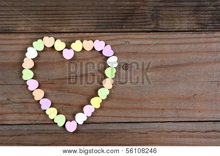 Overhead view of a group of Valentines Day candy on a rustic wood table arranged in a heart shape. Horizontal format with copy space.