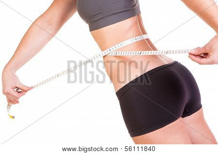 A beautiful young woman using a tape measure to measure her slim waist size on a weight plan