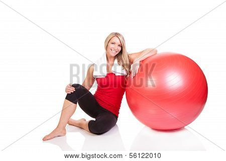 A beautiful young woman resting after exercise on a fitness ball