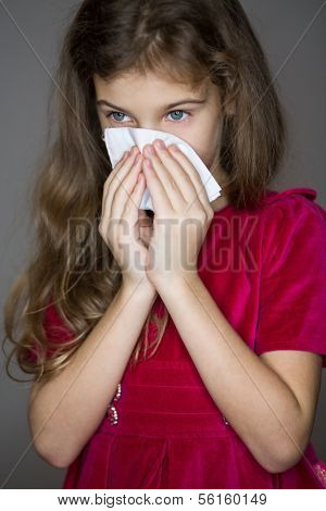 Little girl in red dress wipes her nose with a damp cloth