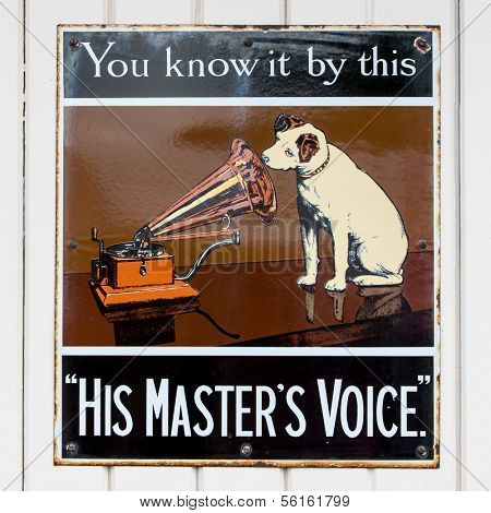 NR SOUTHAMPTON,UK - 25 June 2013: Old style tin advertising board for His Master's Voice displayed on painted wood background. On 25 June 2013 Near Southampton UK