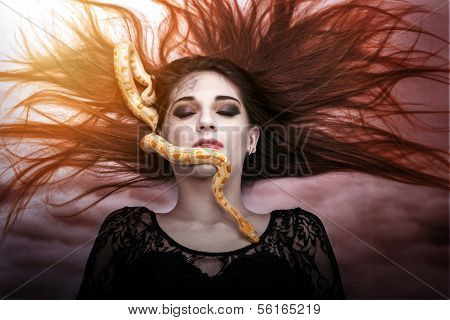 Woman lying on the floor with eyes closed face the snake slither-awesome