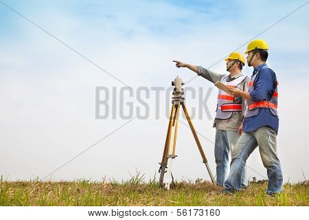 Surveyor engineer making measure with partner on the field. discussing processing poster