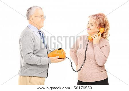 Middle aged couple using old telephone, isolated on white background