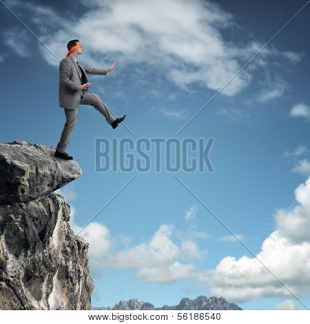 Businessman in a blindfold stepping off a cliff ledge concept for risk, challenge, conquering adversity or ignorance