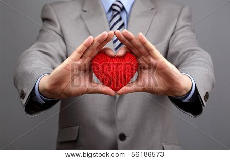 Man holding a red woolen heart concept for valentine's day, business customer care, charity, social and corporate responsibility poster