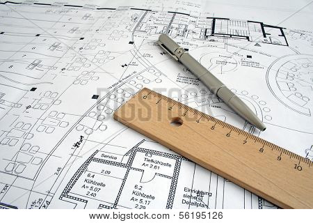 Typical utensils of a draftsman lying on a ground plan.