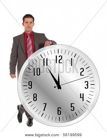 A handsome businessman standing next to a huge clock that shows the eleventh hour. All on white background.