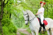 Attractive girl in floral wreath riding horse poster