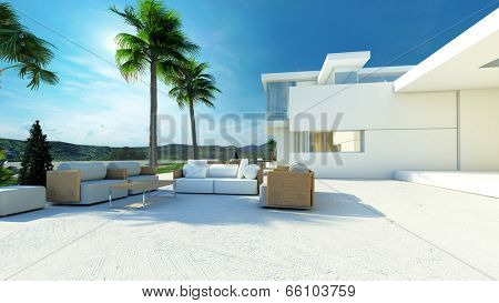 Outdoor paved patio living area with comfortable furniture in the shade of palm trees in a modern tropical luxury villa with white walls