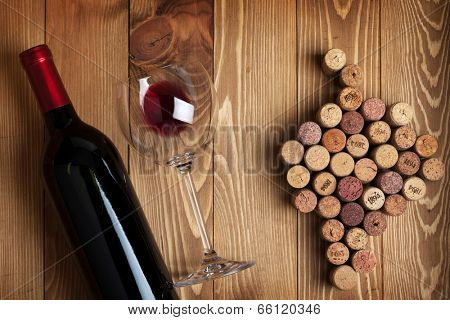 Red wine bottle, glass and grape shaped corks on wooden table background