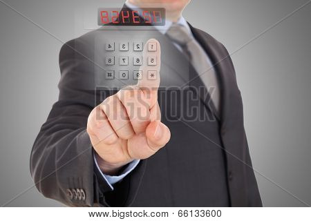 Businessman is setting code of security alarm system