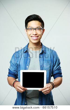 Young cheerful asian man showing tablet computer screen on gray background