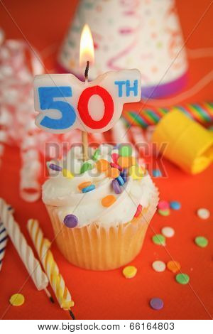 Delicious cupcake with 50th candle on top with hat, candle and noisemaker in background