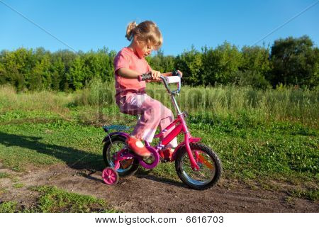 The Little Girl Goes For A Drive On A Pink Bicycle In Park