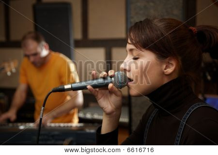 vocalist girl is singing in studio. keyboard player in out of focus